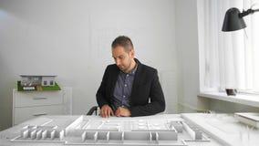 Geschäftsmann schaut die Architektur, die mit vergrößerter und Mischwirklichkeit projektiert wird stock video footage