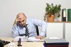 Geschäftsmann schaut durchdacht auf seinem Ordner Lizenzfreies Stockbild
