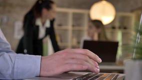 Geschäftsmann schreibt auf Laptop im Büro, seine Kollegen sind Vernetzung mit Technologien, der unscharfe Hintergrund und arbeite stock video