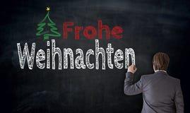 Geschäftsmann schreibt Frohe Weihnachten in deutsche frohe Weihnachten Stockbild