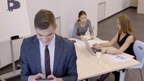 Geschäftsmann schreibt Text auf Tablette im Büro, in dem Personal auf bitcoins rät stock footage