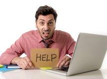Geschäftsmann am Schreibtisch, der an Computerlaptop bitten um die Hilfe hält das Pappzeichen schaut traurig und deprimiert arbei Lizenzfreie Stockbilder
