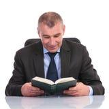Geschäftsmann am Schreibtisch, liest ein Buch Stockbild