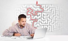 Geschäftsmann am Schreibtisch mit Labyrinth und Pfeil Stockbild