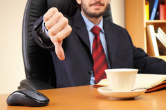 Geschäftsmann an seinem Arbeitsplatz zeigt Daumen unten Lizenzfreie Stockfotos