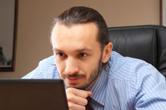 Geschäftsmann an seinem Arbeitsplatzblick im Laptop. Lizenzfreie Stockfotos