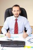 Geschäftsmann an seinem Arbeitsplatzeinfluß greift oben ab Stockfoto