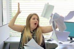 Geschäftsmann an seinem Schreibtisch wirft Dokumente und Papiere in die Luft stockfotos