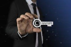 Geschäftsmann in seinen Händen schützen Schlüsselikone über der bunten Unschärfe, Copyright urheberrechtlich und patentieren Konz Lizenzfreies Stockbild
