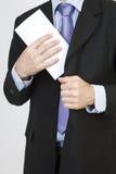 Geschäftsmann setzt einen weißen Umschlag in seine Tasche ein Stockbilder