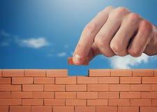 Geschäftsmann setzt einen Ziegelstein, um eine Wand zu errichten Konzept des neuen Geschäfts, der Partnerschaft, der Integration  lizenzfreies stockfoto