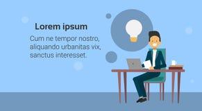 Geschäftsmann Sit At Office Desk Working auf Laptop-Computer an der neuen Idee für Start mit heller Blasen-Ikone Stockbild