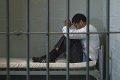 Geschäftsmann Sitting On Bed hinter Gittern Stockfotografie