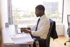 Geschäftsmann-Sitting At Desk-Funktion auf Laptop im modernen Büro lizenzfreies stockfoto