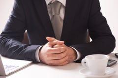 Geschäftsmann Sitting At Desk mit den gefalteten Händen stockbild