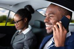 Gesch?ftsmann Sitting Inside Car, das auf Mobiltelefon spricht stockbild