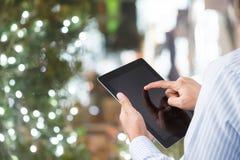 Geschäftsmann sitzen und benutzen Tablette für Arbeit mit bokeh Hintergrund stockfotografie