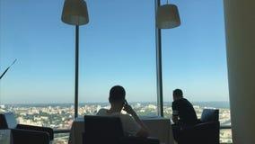 Geschäftsmann-sitzen Unterhaltungszellintelligenter Telefon-Anruf im vorderen panoramischen Fenster-Geschäftsmann-In Coworking Ce stock video