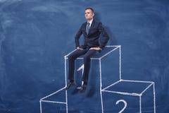 Geschäftsmann sitzt auf dem ersten Platz eines Podiums auf blauem Tafelhintergrund Stockbilder