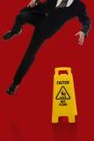 Geschäftsmann Slipping auf nassem Boden Stockfoto
