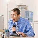 Geschäftsmann spielt Computerspiele im Büro Stockfotos