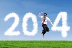 Geschäftsmann springt mit Wolken von 2014 Lizenzfreies Stockfoto