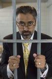 Geschäftsmann-Standing Behind Prison-Zellstangen Stockbild