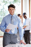 Geschäftsmann Standing In Boardroom, das Dokument verwahrt Stockfotografie