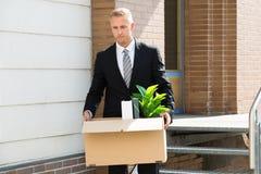 Geschäftsmann-Standing With Cardboard-Kasten Stockfoto