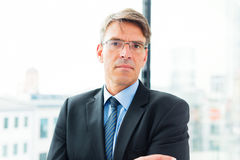 Geschäftsmann-Standing By The-Fenster Lizenzfreie Stockbilder