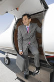 Geschäftsmann Standing On Ladder des privaten Flugzeuges Lizenzfreies Stockbild