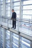 Geschäftsmann Standing By Railing im modernen Büro Stockfoto