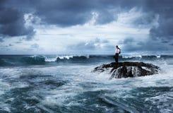 Geschäftsmann Stay Alone auf dem Felsen lizenzfreie stockbilder