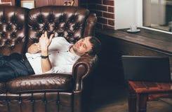 Geschäftsmann steht auf einem ledernen Sofa nahe einem Laptop mit einer Tasse Tee im Raum still Der Mann hält das Telefon in sein stockfoto