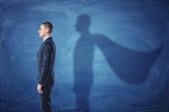 Geschäftsmann steht im Profil, das einen Schatten des Supermann ` s Kaps auf blauem Tafelhintergrund wirft Stockfotografie