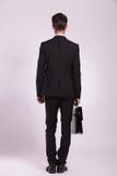 Geschäftsmann steht mit Aktenkoffer Stockbild