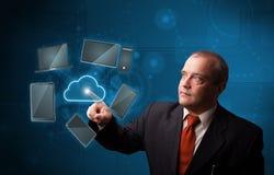 Geschäftsmann-Stellung und rührende Spitzentechnologie Stockfoto