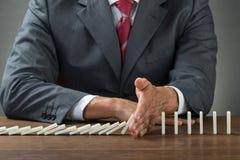 Geschäftsmann Stopping Dominoes Falling auf hölzernem Schreibtisch Stockfoto