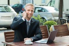 Geschäftsmann Talking On Cellphone, das Laptop betrachtet lizenzfreies stockbild