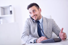 Geschäftsmann am Telefon bei der Anwendung des Laptops im Büro Lizenzfreies Stockfoto
