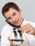 Geschäftsmann am Telefon, das einen Kartenhalter anhält Lizenzfreie Stockfotografie