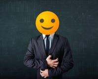 Geschäftsmann trägt gelbes smileygesicht Stockbild