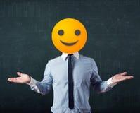Geschäftsmann trägt gelbes smileygesicht Lizenzfreies Stockbild