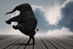 Geschäftsmann tragen Elefanten allein unter blauem Himmel Lizenzfreie Stockfotografie