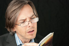 Geschäftsmann-tragendes Glas-Lesebuch Lizenzfreie Stockfotografie