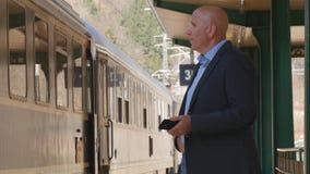 Geschäftsmann In Train Station, das Passagiere sucht stockfoto