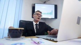 Geschäftsmann trinkt coffe beim Aufpassen des Laptopschirmes lizenzfreies stockfoto