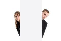 Geschäftsmann u. Frau, die hinter einem Anzeigenplatz sich verstecken stockfotografie