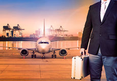 Geschäftsmann und breifcase, die gegen Transportflugzeug in Transport stehen Stockbild