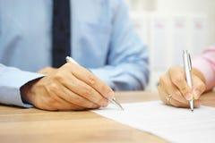 Geschäftsmann und Frau übergeben unterzeichnende Vereinbarung im Büro Stockbild